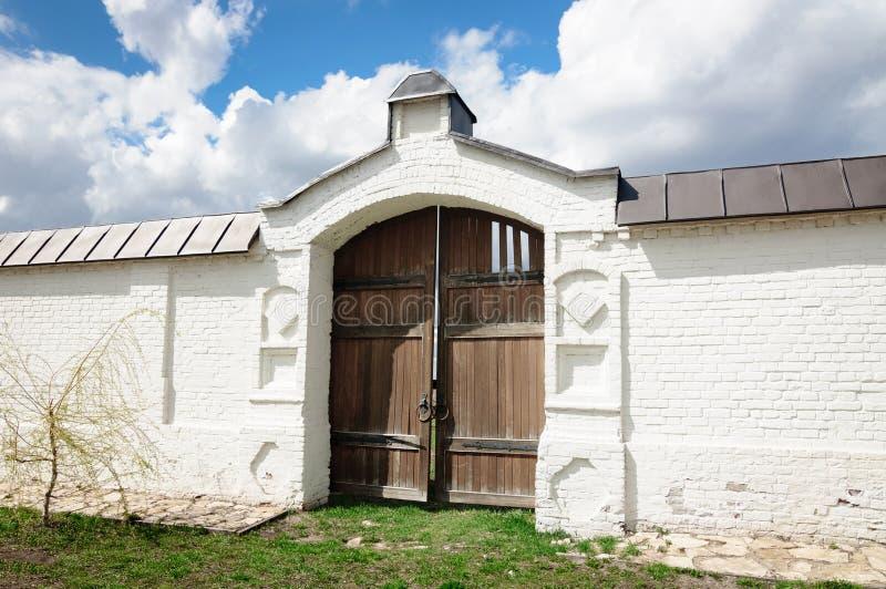 Старые деревянные ворота в белой каменной стене стоковое изображение rf