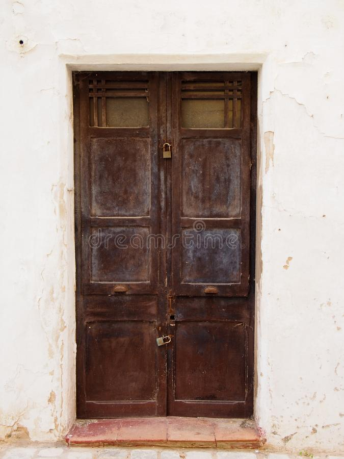 Старые деревянные коричневые двойные двери с откалыванный шелушиться увяли слезающ краску и ржавые ручки padlocked закрытое в бел стоковая фотография