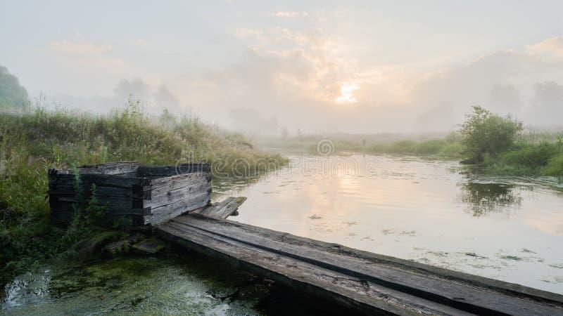 Старые деревянные колодец и мост через малое реку на лете пасмурном s стоковое изображение rf