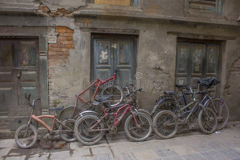 Старые затрапезные велосипеды различных размеров стоят на улице около поврежденной стены стоковые изображения rf