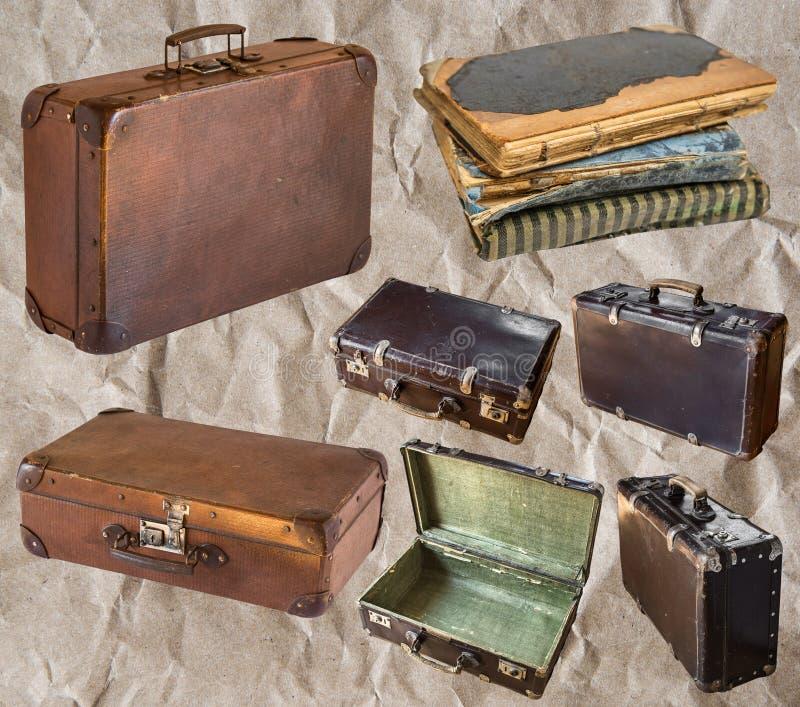 Старые затрапезные винтажные чемоданы и книга изолированные на серой предпосылке r стоковое изображение rf