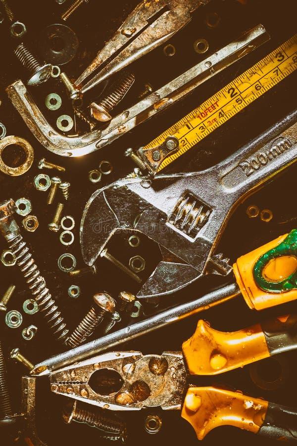 Старые инструменты и винты на металлической предпосылке стоковое изображение rf