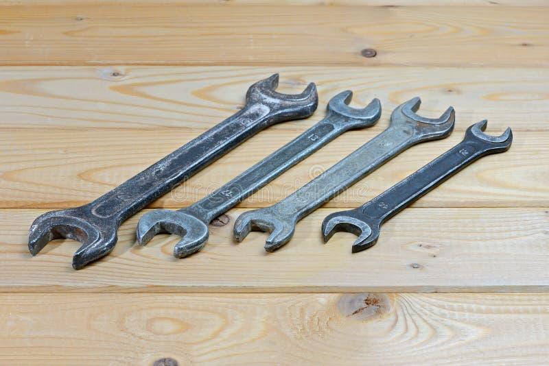 Старые используемые ключи на деревянной предпосылке Винтажные гаечные ключи стоковая фотография