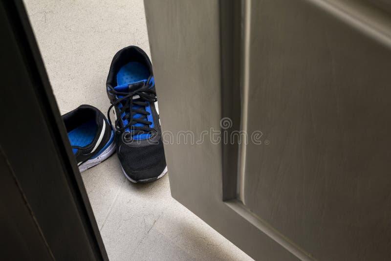 Старые и грязные голубые тапки холста во входе к комнате стоковое фото