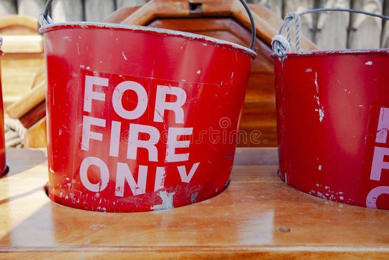 Старые и несенные ведра красного огня в деревянной стойке стоковые изображения rf