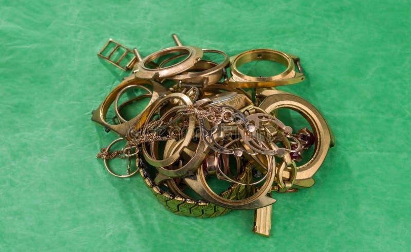 Старые и сломленные ювелирные изделия, вахты золота на зеленом цвете стоковые фото