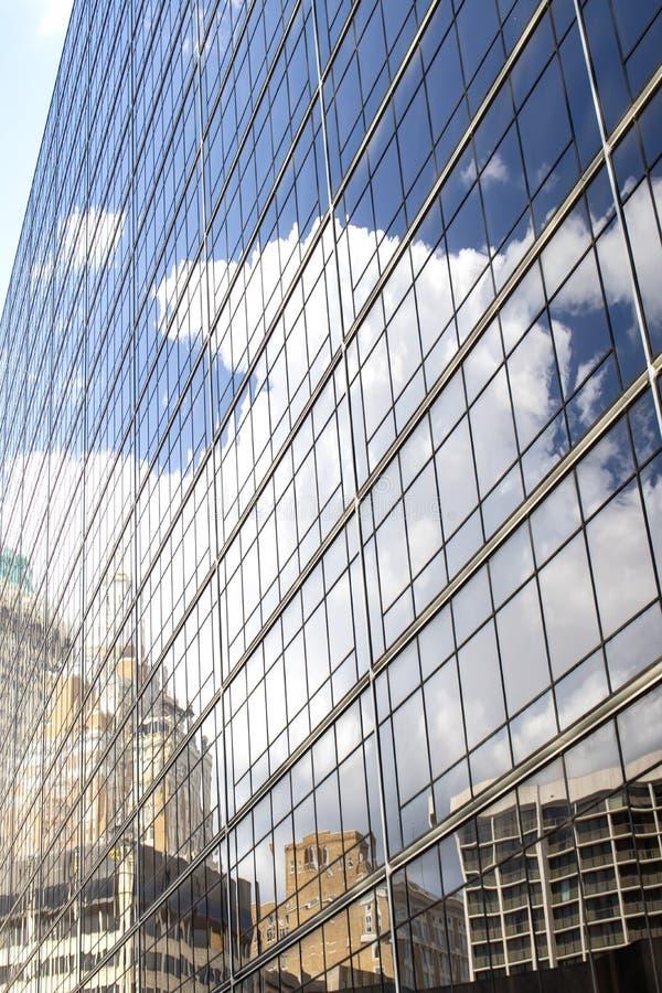 Старые и современные здания и очень голубое небо с возвышаясь белыми пушистыми облаками отражены в стороне высокорослого стеклянн стоковое фото