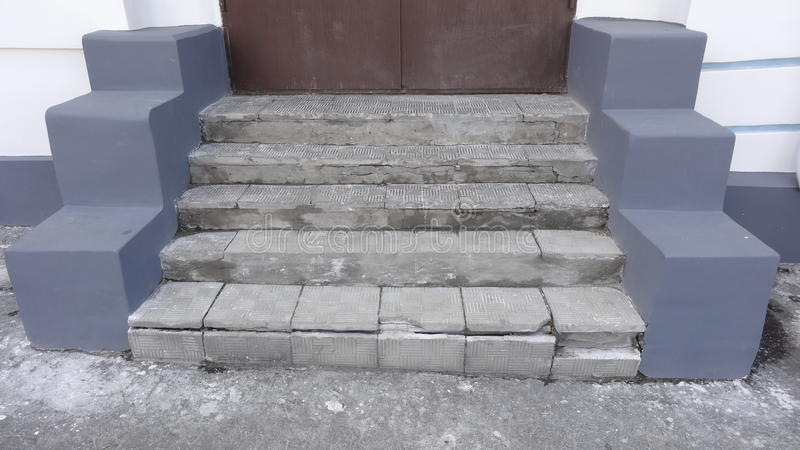 Старые каменные серые шаги с знаками носки разрушения с царапинами и отказами к красной двери на улице стоковое изображение