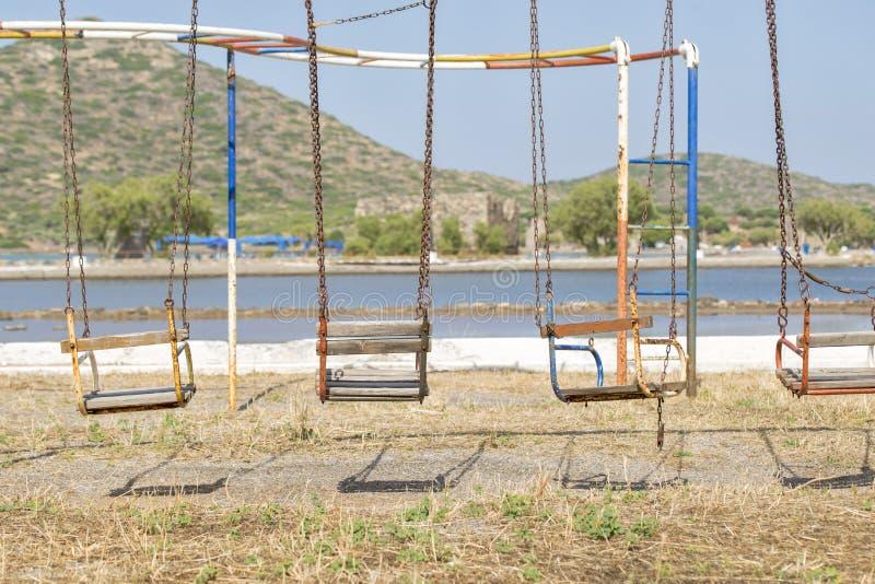 Старые качания в спортивной площадке около моря стоковые фото