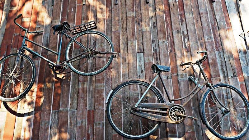 Старые классические велосипеды вися на деревянной стене стоковые фотографии rf