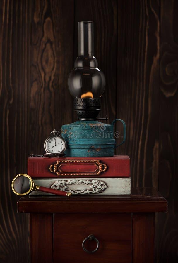Старые книги, масляная лампа и винтажный дозор на цепи стоковая фотография
