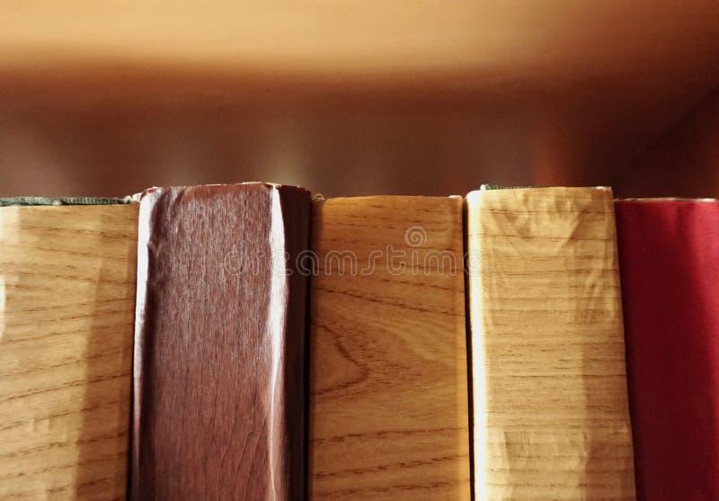 Старые книги покрыли с поврежденный защищают бумагу, который держат совместно на книжных полках стоковые изображения