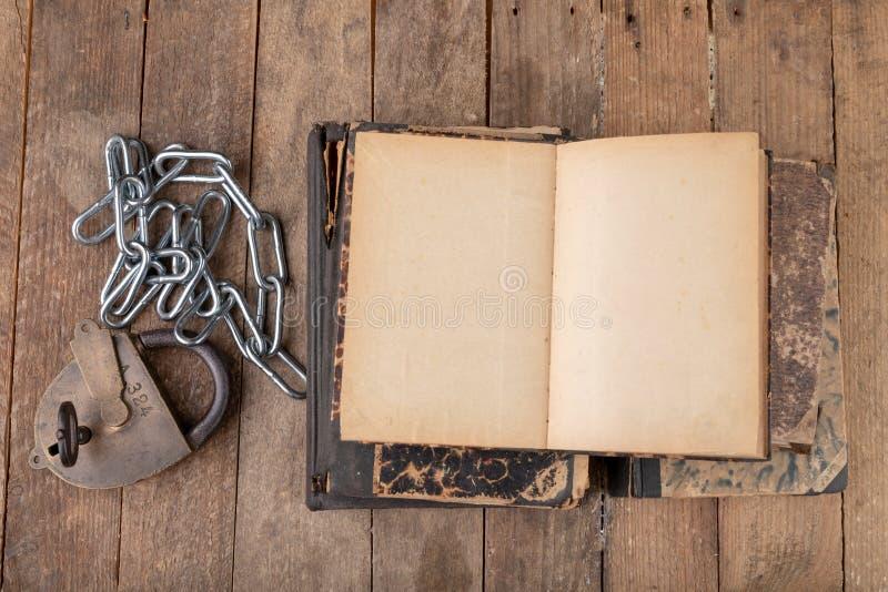 Старые книги прыгнутые новой сияющей цепью со старым padlock Запрещенные старые художники работ на деревянном столе стоковое фото rf