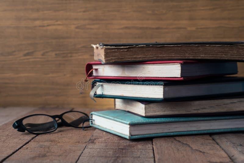 Старые книги hardback с стеклами на деревянном столе стоковое фото rf