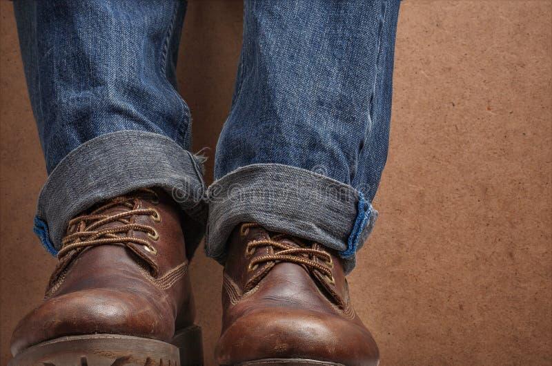 Старые кожаные коричневые ботинки и голубые джинсы стоковые фотографии rf