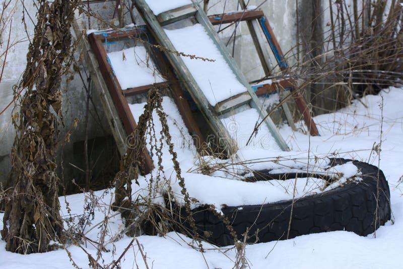 Старые колеса тележки в зиме в покинутое стоковое изображение
