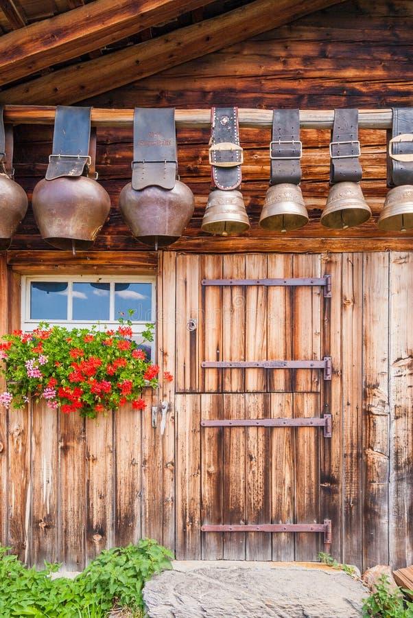 старые колоколы коровы под крышей высокогорной хаты горы, Швейцарии стоковые фотографии rf