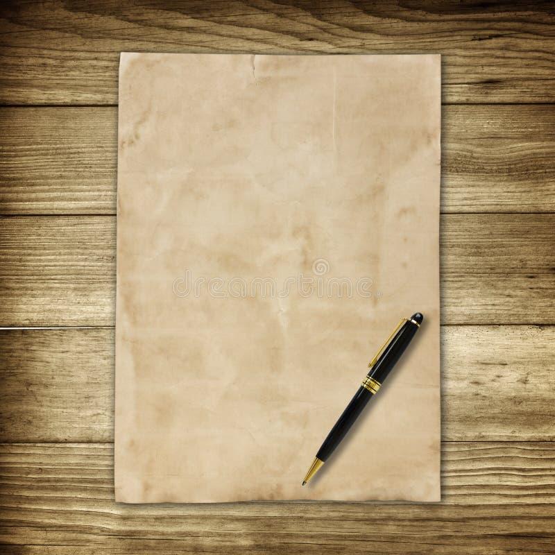 Старые коричневая бумага и ручка на деревянной предпосылке стены для текстуры стоковая фотография