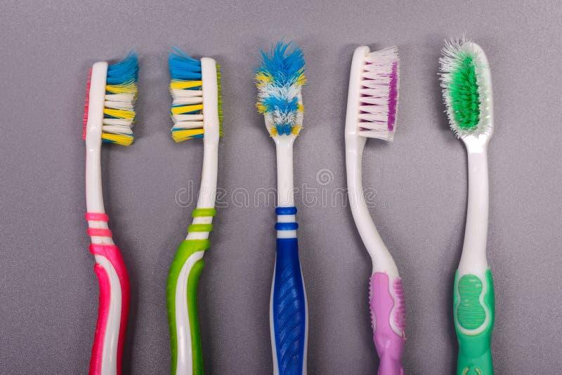 Старые красочные зубные щетки на серой предпосылке стоковые фотографии rf