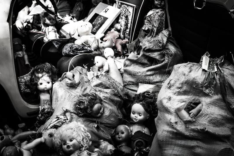 Старые куклы сбросили в куче на желтом автомобиле, погани игрушек детей стоковые фотографии rf