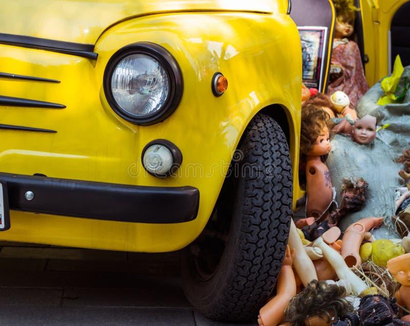 Старые куклы сбросили в куче на желтом автомобиле, погани игрушек детей стоковое изображение