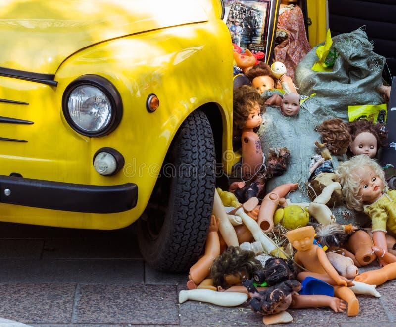 Старые куклы сбросили в куче на желтом автомобиле, погани игрушек детей стоковое фото rf