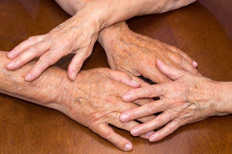 Старые люди держа руки closeup стоковые изображения