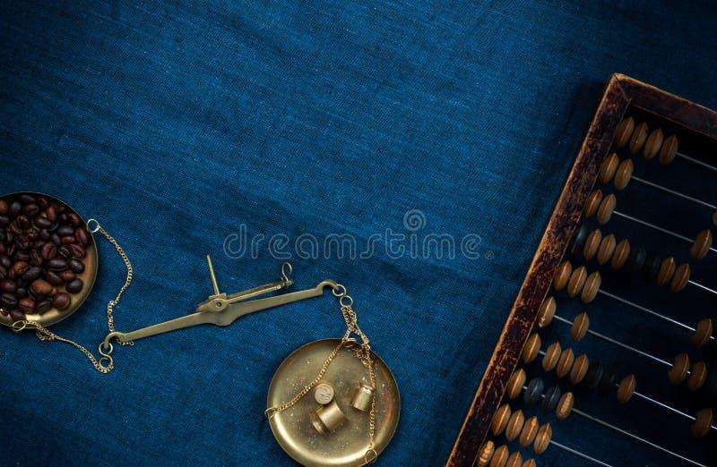 Старые масштабы руководства с маленькими счетами весов и кофейных зерен на голубой ткани стоковая фотография rf