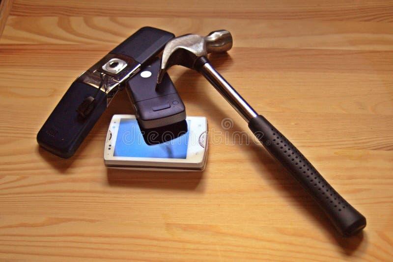Старые мобильные телефоны с молотком стоковое фото