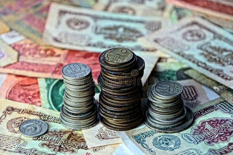 Старые монетки в кучах на счетах бумажных денег стоковое изображение