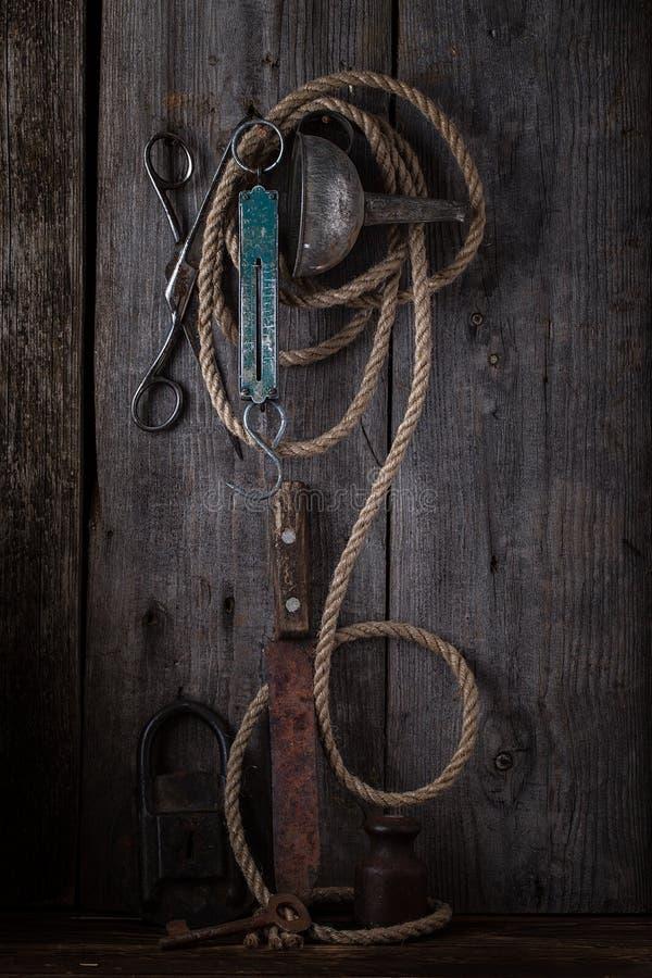 Старые ножницы и смертная казнь через повешение веревочки на деревянной стене стоковая фотография rf