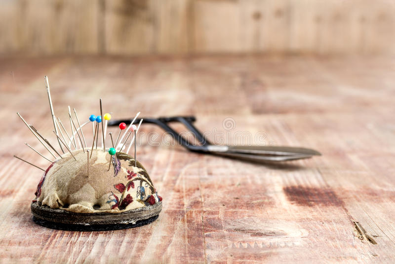Старые ножницы и pincushion на деревянной предпосылке стоковые изображения