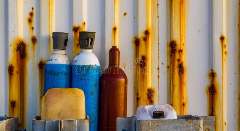 Старые обжатые жидкостные баллоны для сжатого воздуха стоя перед ржавым контейнером, промышленной предпосылкой стоковые фото