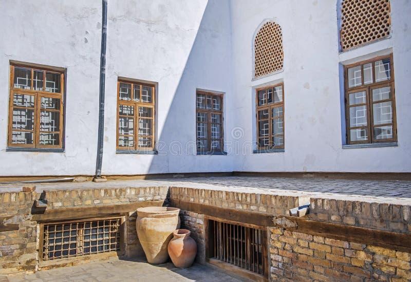 Старые окна решетки в белой стене и больших кувшинах глины во внутреннем дворе старого ковчега Бухары, Узбекистана стоковые фотографии rf