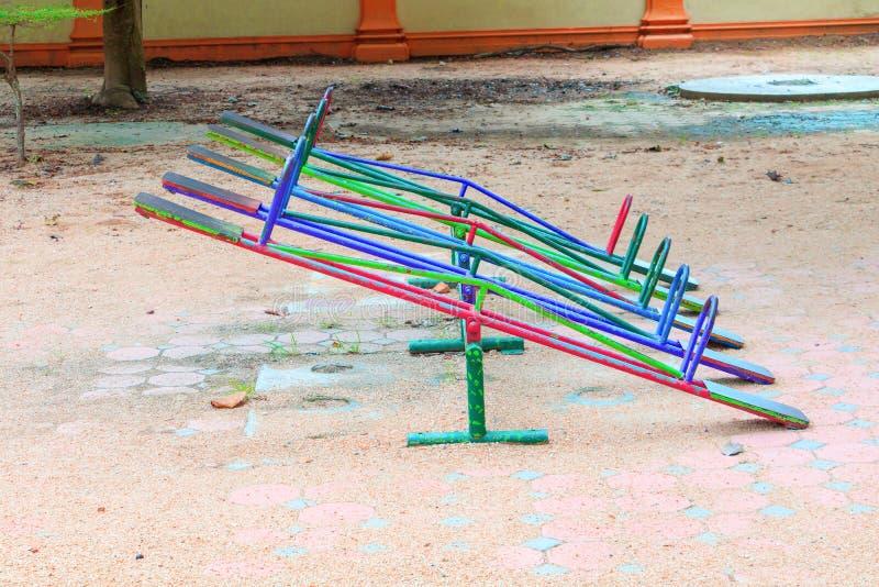Старые опущенные деревья или металл спортивной площадки seesaw традиционный в сельской местности ребеят школьного возраста стоковые фотографии rf