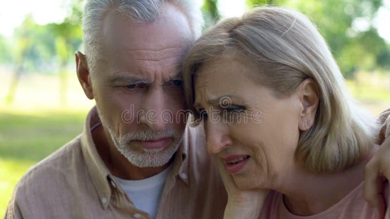 Старые пары плача и обнимая, поддерживая один другого в заболевании, бедности, потере стоковые изображения