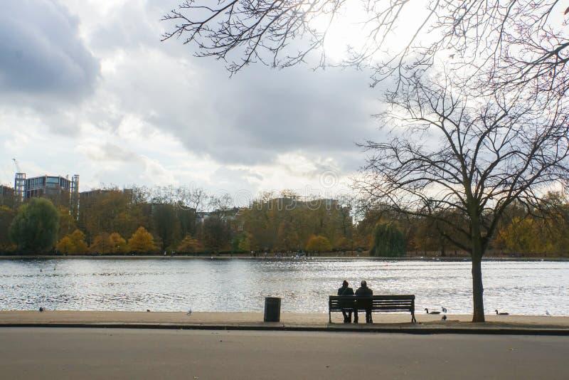 Старые пары сидят на стенде в парке стоковое фото