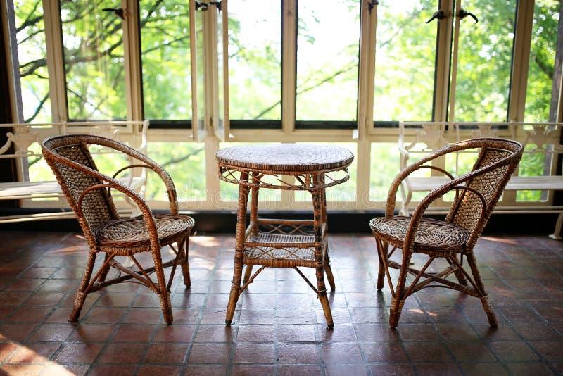 Старые плетеные таблица и стулья бистро в патио комнаты Солнця исторического стоковое фото rf