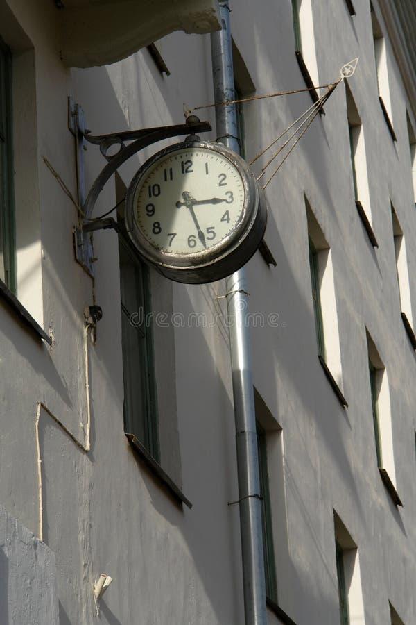 Старые разрушанные серые часы улицы на стене здания Затрапезный механический дозор стены с царапинами стоковые фото