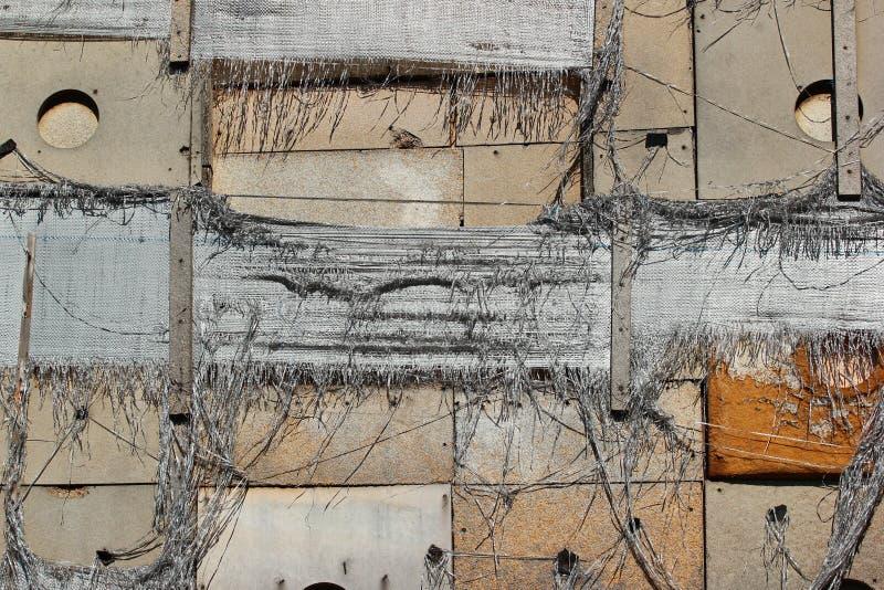 Старые растрепанные панели изоляции, сорванные мешочки из ткани нейлона и деревянные plamks на стене покинутого здания стоковое изображение
