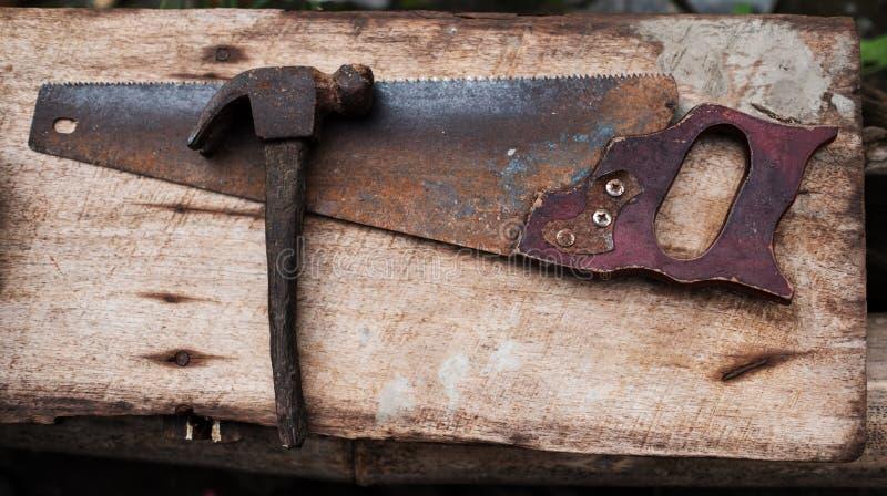 Старые ржавые инструменты бьют молотком и ручная пила для работы стоковая фотография rf