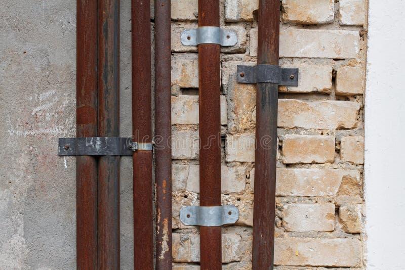 Старые ржавые трубы металла на кирпиче и бетонной стене стоковое изображение rf