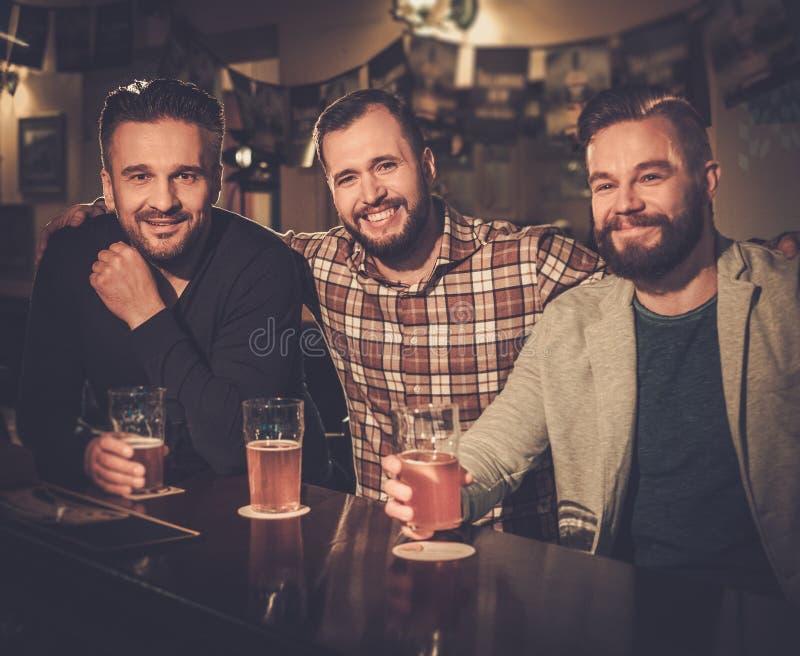 Старые други выпивая пиво проекта на счетчике бара в пабе стоковые изображения rf