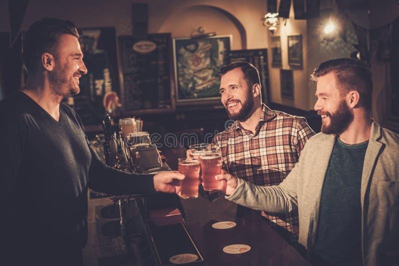 Старые други выпивая пиво проекта на счетчике бара в пабе стоковые фото