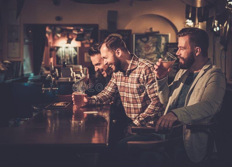 Старые други имея потеху и выпивая пиво проекта на счетчике бара в пабе стоковое изображение