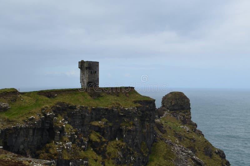 Старые руины башни на скалах моря в Ирландии стоковые изображения
