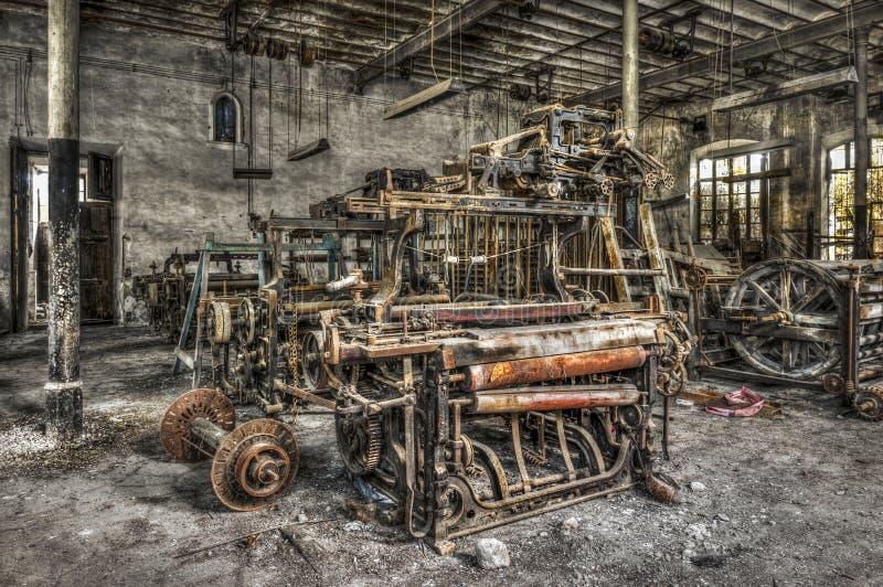 Старые сплетя тени и закручивая машинное оборудование на покинутой фабрике ткани стоковая фотография