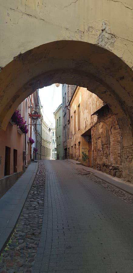 Старые улицы Вильнюса на которые люди различных времен шли стоковая фотография