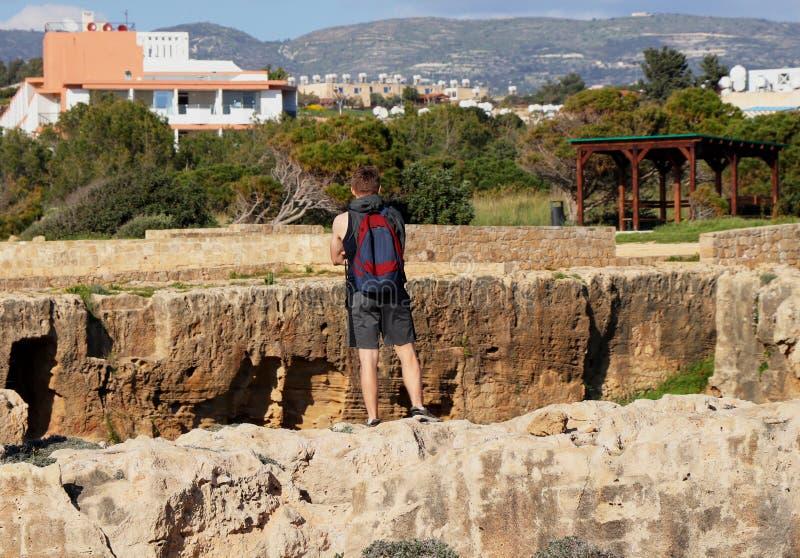 Старые усыпальницы руин королей в Paphos, Кипре Молодой туристский взгляд вниз в одну из много усыпальниц в этом историческом пар стоковые фото
