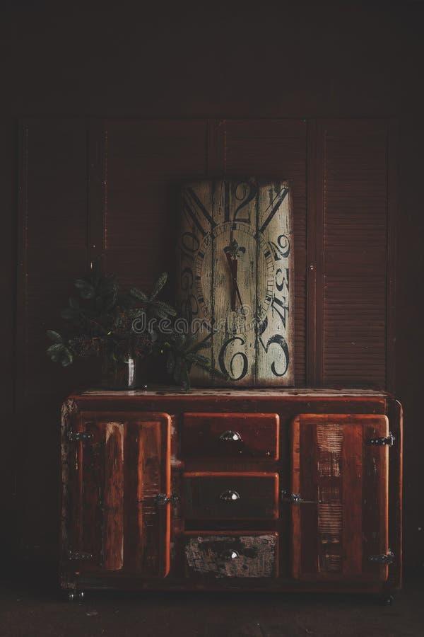 Старые часы и букет рождества ветвей ели на старом комоде ящиков стоковые фотографии rf